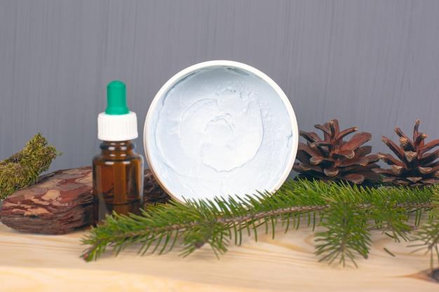 Ekologiczne kosmetyki do pielęgnacji ciała, peeling do ciała i olejki eteryczne, szyszki i gałązka sosny na szarym tle.
