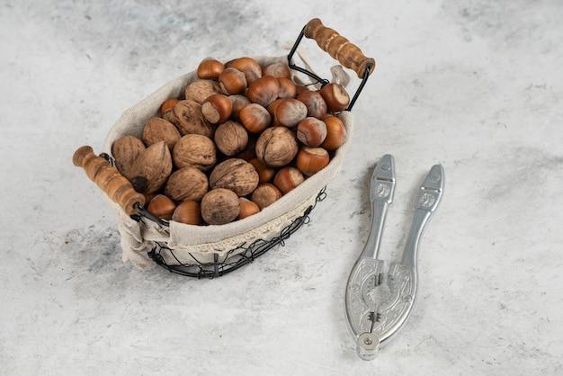Ekologiczne łuskane orzechy laskowe i orzechy włoskie w koszyku z narzędziem do łupania orzechów.