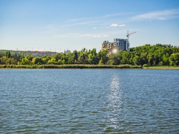 Ekologiczne mieszkania na terenie parku. budynki w pobliżu jeziora. budowa nowoczesnych budynków. koncepcja ekologicznego mieszkania.