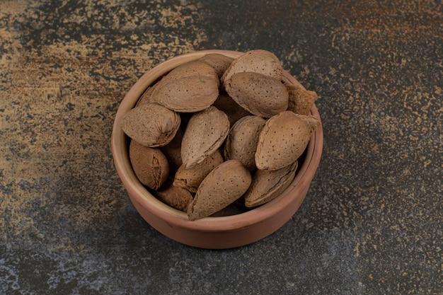 Ekologiczne migdały łuskane w ceramicznej misce.