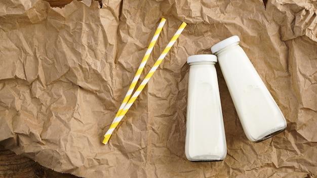 Ekologiczne mleko krowie w szklanych butelkach. dwie butelki mleka na zmiętym papierze rzemieślniczym. dwie żółte papierowe słomki do picia. naturalne mleko dla zdrowia.