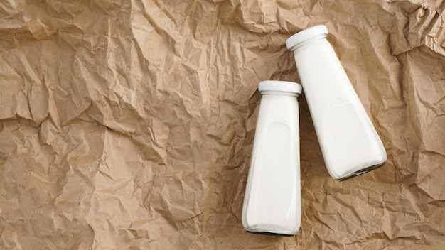 Ekologiczne mleko krowie w szklanych butelkach. dwie butelki mleka na zmiętym papierze rzemieślniczym. naturalne mleko dla zdrowia.