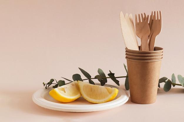 Ekologiczne naczynia kuchenne w stosie tekturowych kubków i talerzyku z cytrynami na jasnobeżowym tle