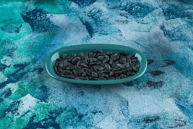 Ekologiczne nasiona słonecznika w talerzu, na niebieskim stole.