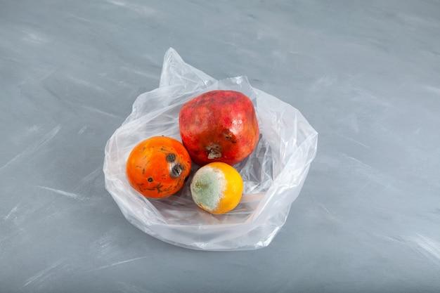 Ekologiczne odpady żywnościowe zgniłe owoce w plastikowej torbie koncepcja niedoskonałe przechowywanie warzyw i owoców