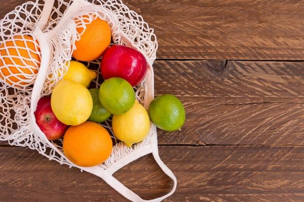 Ekologiczne owoce w bawełnianej siatce na drewnianym stole, torba na zakupy wielokrotnego użytku. zrównoważony styl życia i koncepcja zero odpadów. skopiuj miejsce na tekst.