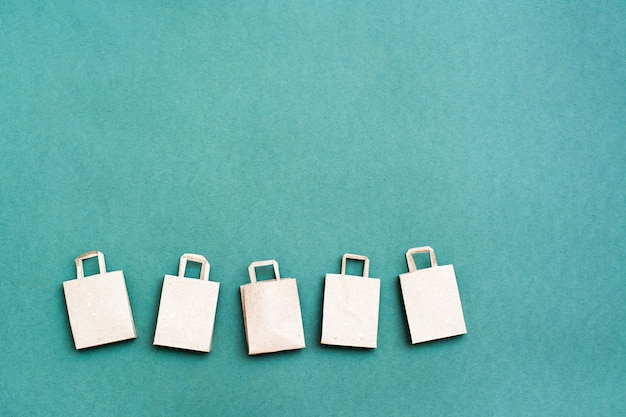 Ekologiczne papierowe torby na zakupy z rzędu na zielonym tle. sprzedaż prezentów w czarny piątek. skopiuj miejsce