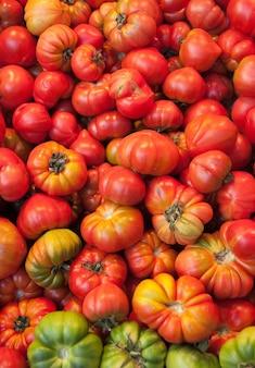 Ekologiczne pomidory o nieregularnym kształcie w odcieniach czerwieni i zieleni