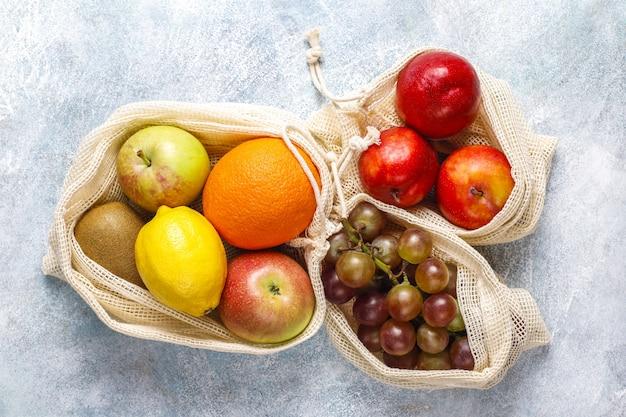 Ekologiczne, proste, beżowe bawełniane torby na zakupy do kupowania owoców i warzyw z letnimi owocami.
