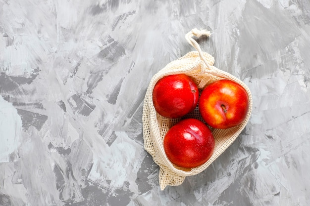 Ekologiczne, proste beżowe bawełniane torby na zakupy do kupowania owoców i warzyw z letnimi owocami.