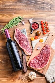 Ekologiczne steki wołowe picanha nad starym amerykańskim tasakiem rzeźniczym z przyprawami i butelką czerwonego wina na drewnianym stole. widok z góry.