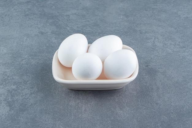 Ekologiczne surowe jajka w białej misce.