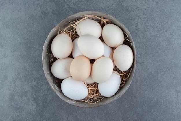 Ekologiczne surowe jajka w metalowej misce.