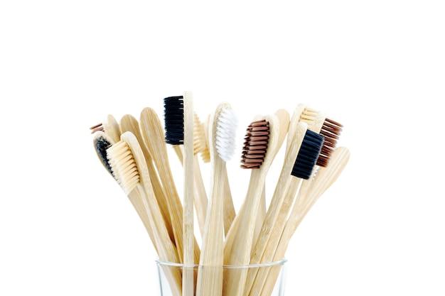 Ekologiczne szczoteczki do zębów w przezroczystym szkle na białym tle