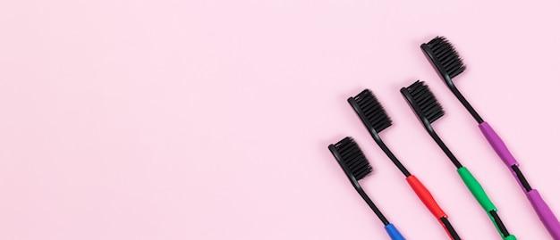 Ekologiczne szczoteczki do zębów wykonane z biodegradowalnego tworzywa oraz bambusowego węgla aktywnego na różowym tle. baner z miejsca na kopię
