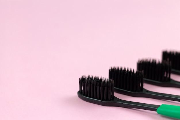 Ekologiczne szczoteczki do zębów wykonane z biodegradowalnego tworzywa oraz bambusowego węgla aktywnego na różowym tle