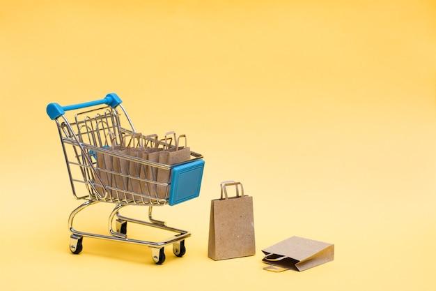 Ekologiczne torby na zakupy z papieru kraft w koszyku i obok niego na żółtym tle. sprzedaż prezentów w czarny piątek. skopiuj miejsce
