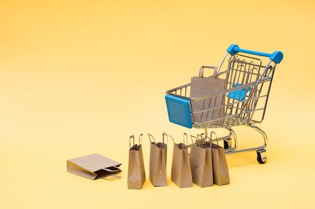 Ekologiczne torby na zakupy z papieru kraft w koszyku i obok niego na żółtym tle. wyprzedaż prezentów w czarny piątek
