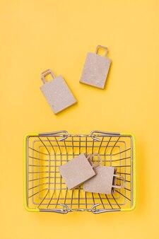 Ekologiczne torby papierowe rzemieślnicze w metalowym koszu na zakupy i w jego pobliżu na żółtym tle. czarny piątek, sprzedaż prezentów. widok z góry i z pionu