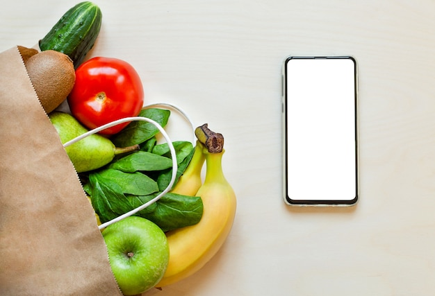 Ekologiczne warzywa i owoce w torbie rzemieślniczej i telefonie, koncepcja dostawy żywności do domu.