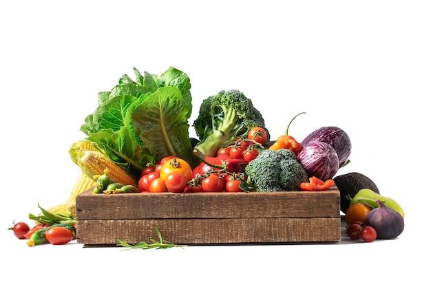 Ekologiczne warzywa i warzywa w drewnianym pudełku na białym tle
