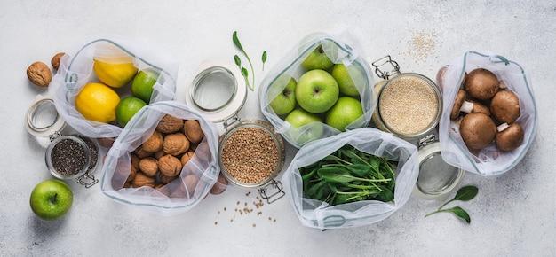Ekologiczne zakupy z torbami wielokrotnego użytku i szklanymi słoikami. pakowane zdrowe produkty wegańskie
