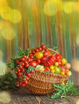 Ekologiczne zielone, czerwone, żółte, pomarańczowe pomidory w drewnianym koszu. ukraińskie życie na wsi.