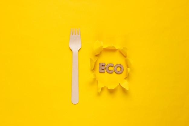 Ekologiczny drewniany widelec na żółtym tle. słowo eko na papierze z rozdartym otworem. minimalizm.