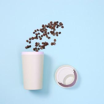 Ekologiczny kubek wielokrotnego użytku z palonymi ziarnami kawy. koncepcja zero waste, płaska konstrukcja. zabierz duży kubek na napoje
