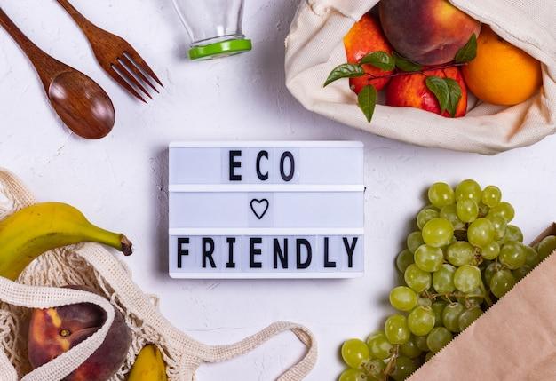Ekologiczny napis na tablicy obok owoców w ekologicznych torebkach