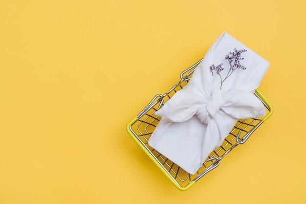 Ekologiczny prezent furoshiki i suszone kwiaty w metalowym koszu na zakupy na żółtym tle. czarny piątek, sprzedaż prezentów. widok z góry. skopiuj miejsce