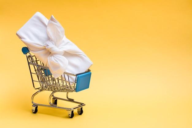 Ekologiczny prezent furoshiki w koszyku na żółtym tle. wyprzedaż prezentów w czarny piątek
