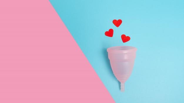 Ekologiczny różowy kubek menstruacyjny wielokrotnego użytku z serduszkami imitującymi krew menstruacyjną na niebiesko-różowym tle. mieszkanie leżało z miejscem na kopię. świadomość ekologiczna, przyjazna dla środowiska, koncepcja zero odpadów