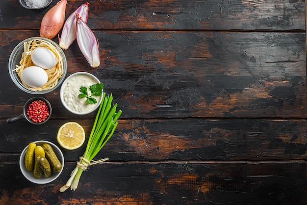 Ekologiczny sos ranczo cytrynowy sos tatarski. z dodatkiem kaparów, ogórków, pietruszki, cytryny i jajek. widok z góry na ciemne drewno rustykalne stare miejsce na tekst
