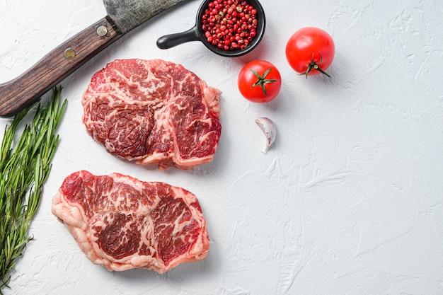 Ekologiczny stek top blade, surowe mięso wołowe z przyprawami, rozmarynem i tasakiem rzeźniczym. białe tło z teksturą. widok z góry miejsca na tekst.