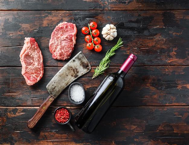 Ekologiczny stek z górnego ostrza, surowe mięso wołowe z przyprawami, rozmarynem i tasakiem rzeźniczym oraz butelka czerwonego wina. drewno teksturowane tło. widok z góry miejsca na panoramę tekstu.