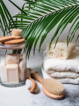 Ekologiczny zestaw do kąpieli. pędzle, mydło w słoiku, ręcznik, pumeks i łyk oraz liście palmowe