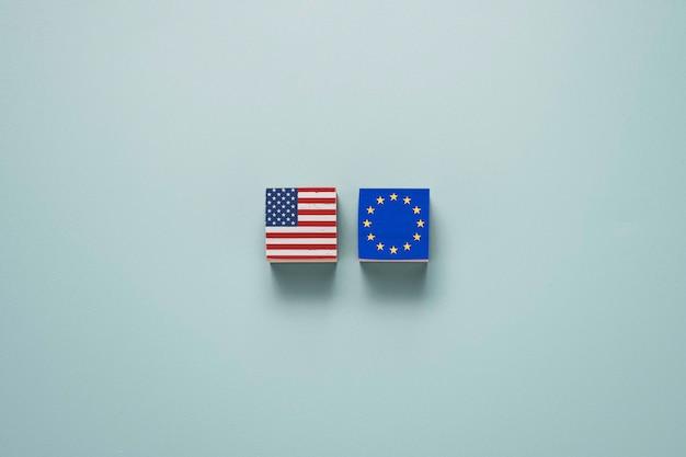 Ekran drukowania flagi usa i euro na drewnianych kostkach na niebiesko