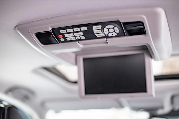 Ekran m panel sterowania systemu multimedialnego na białym suficie nowoczesnego samochodu. zbliżenie