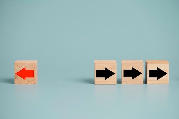 Ekran nadruku czerwonej strzałki na drewnianym bloku zmienia kierunek od prawej do lewej, który różni się od czarnych strzałek