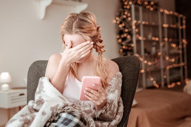 Ekran smartfona. jasnowłosa wysportowana dziewczyna zakrywająca twarz dłonią w haniebnym geście podczas oglądania mediów społecznościowych