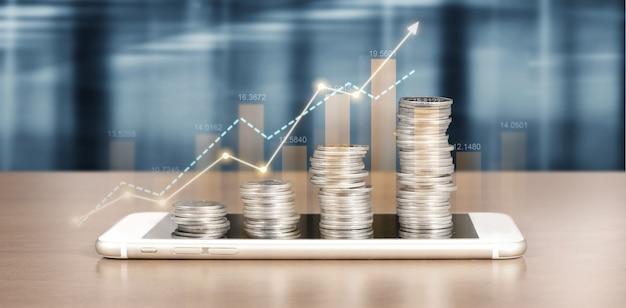 Ekran smartfona obok rosnących stosów monet i wykresu pozytywnych wskaźników w jego biznesie