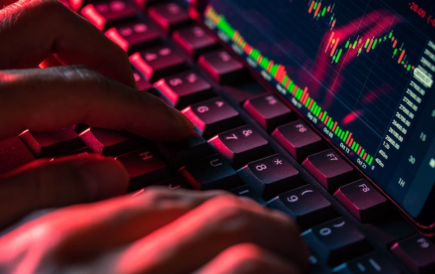 Ekran wykresu giełdowego na klawiaturze komputera i dotykają palcami, koncepcja inwestycji online