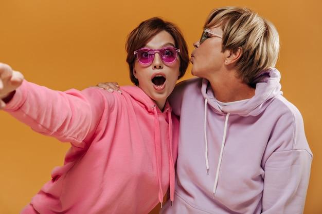 Ekscytująca dziewczyna w jasnych okularach przeciwsłonecznych i różowej bluzie robi selfie ze stylową blondynką na pomarańczowym tle na białym tle.