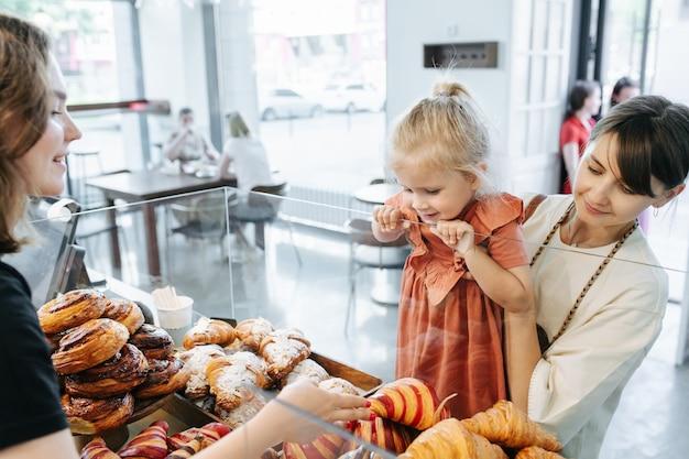 Ekscytująca dziewczynka patrzy na kolorowe rogaliki, wybiera to, czego chce, podczas gdy mama trzyma ją w dłoniach. kasjer uśmiecha się do nich.