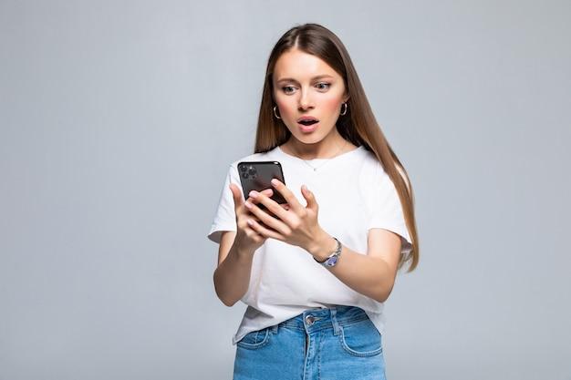 Ekscytująca kobieta czytająca wiadomość tekstową w telefonie na białym tle na szarej ścianie