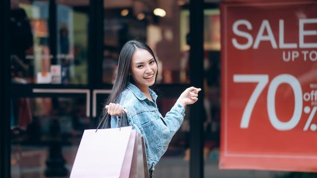 Ekscytująca kobieta wskazuje zakupy deska w zakupy.
