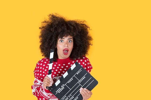 Ekscytująca młoda kobieta trzyma klasyczny czarny karton, na białym tle na jasnożółtym tle, portret studyjny. szczęśliwego nowego roku koncepcja szczęśliwej imprezy
