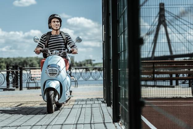 Ekscytująca podróż. cieszę się, że pozytywny facet jedzie na motocyklu i uśmiecha się