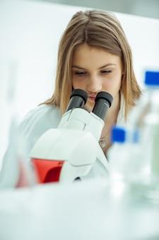 Eksperci laboratoryjni pracujący nad mikroskopem